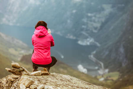 Tourism vacation and travel. Female tourist enjoying Geirangerfjord and mountains landscape from Dalsnibba viewpoint, Norway Scandinavia.
