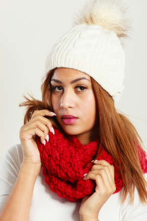 Winter clothing, fashion concept. Beautiful young mulatto woman wearing red woolen scarf white cap. Mixed race girl in wintertime clothes portrait, studio shot