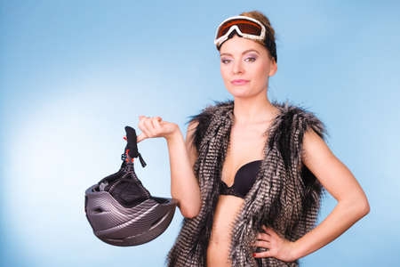 atractive: Winter sport activity concept. Atractive smiling girl wearing black bra, ski goggles and furry waistcoat holding helmet, blue background studio shot.
