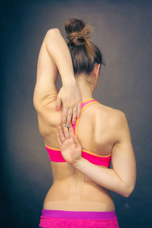 taping: Fit muscular woman with kinesiotaping application for back pain. Backache alternative kinesio tape therapy method. Health and body care.