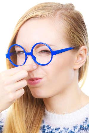 olores apestosos, concepto obstruido. Mujer Nerdy en vidrios divertidos grandes que sostienen la nariz que huele mal olor