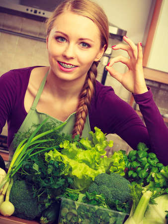 Woman in kitchen with many green leafy vegetables making thumb up hand sign gesture. Young housewife adding to her diet foods high in chlorophyll. Healthy eating, cooking, vegan food concept.