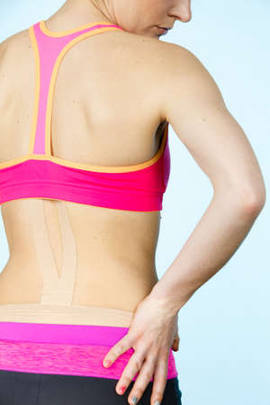 taping: Woman with kinesiotaping application for back pain. Backache alternative kinesio tape therapy method. Health and body care. Stock Photo