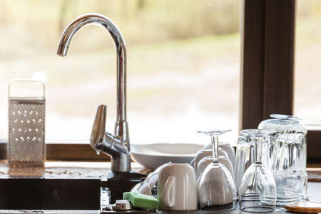 claen: Washing up. Modern sink and kitchen counter with claen dishwares, window in the background