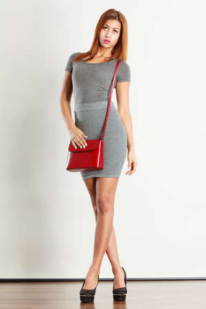 Female fashion. Girl mixed race in full length wearing fashionable gray outfit high heels shoes with red leather bag handbag. Studio shot