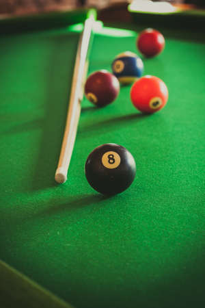 Billiard balls and cue stick on green table. Pool game Stock Photo