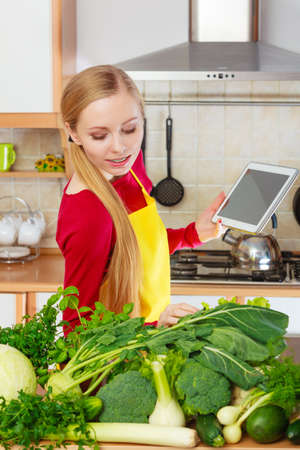 Young woman in kitchen having many green vegetables on table, holding tablet thinking about cooking something and searching for recipes in internet Stock Photo