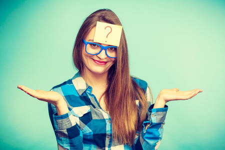 nerdy: Thinking woman with big nerdy eyeglasses and question mark on forehead. Creating new idea, studying and education concept. Stock Photo