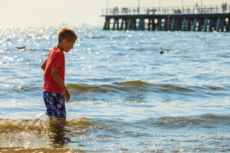 careless: Water fun and joy outside. Little boy walking through the sea ocean. Lonely kid playing outdoors in summer clothes. Stock Photo