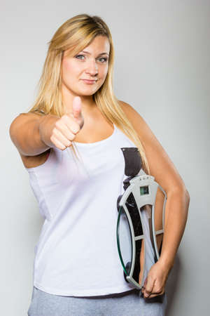 Diet, fitness, slimming, loosing weight concept. Happy blonde woman holding weighing machine showing thumb up gesture.