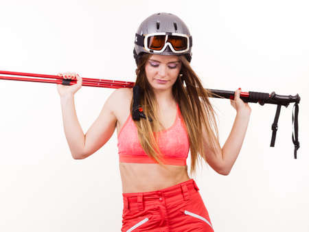 Sensual attractive femine, winter sport concept. Woman wearing alluring ski suit and helmet with goggles holding poles