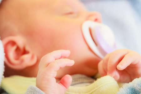 opieki nad noworodkiem, piękno koncepcji dzieciństwa. Mała noworodek śpi spokojnie w łóżku ze smoczkiem w ustach. Zdjęcie Seryjne