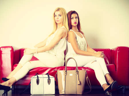 red sofa: Fashion, clothes, clothing accessories, trendy outfits concept. Two women wearing light outfit and black high heels sitting on red sofa presenting bags