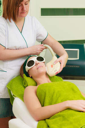 Medical cosmetology, modern cosmetic devices concept. Woman wearing safety glasses, getting laser treatment on her face in beautician