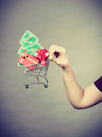 christmas spending: Xmas, seasonal sales, winter celebration concept. Woman hand holding shopping trolley cart basket with little christmas tree and gifts inside.