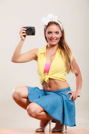 hairband: Happy smiling pretty pin up girl wearing hairband bow, skirt and high heels taking photo picture with camera. Attractive gorgeous young retro woman photographing.