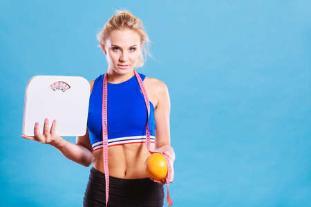 Loosing weight, diet and healthy nutrition. Fit fitness woman with measure tape holding weight scale in one and grapefruit in another hand, on blue