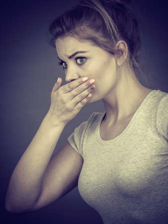 gasping: Woman covering her mouth with hand. Seeing something shocking, surprised and speechless face expression.