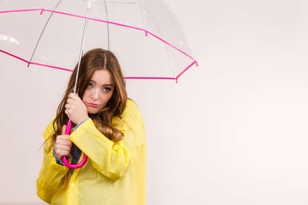 Woman rainy girl wearing waterproof yellow coat standing frozen under transparent umbrella looking sad unhappy. Meteorology, forecasting and weather season.