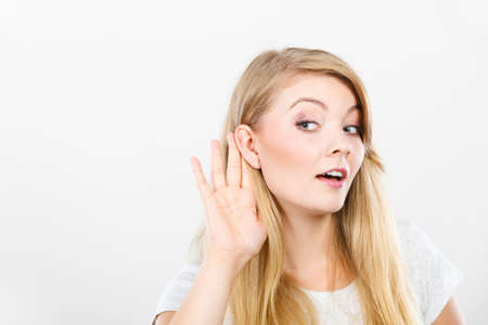 Gossip,rumors, whisper, hearing concept. Young blonde Woman putting hand ear to hear better. Studio shot on white background.