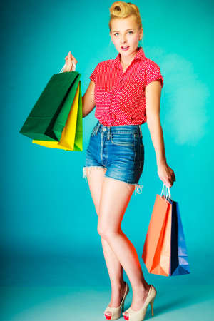Buying things, shopaholic, spending money on clothes concept. Retro vintage young woman with lot of shopping bags. Studio shot on blue background Stock Photo