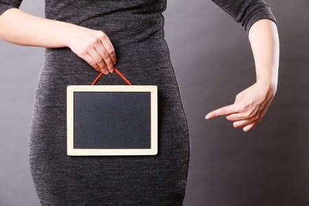 Feminine body problems concept. Woman holding blank black board on crotch, grey background.