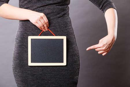 Feminine body problems concept. Woman holding blank black board on crotch, grey background. Stock Photo