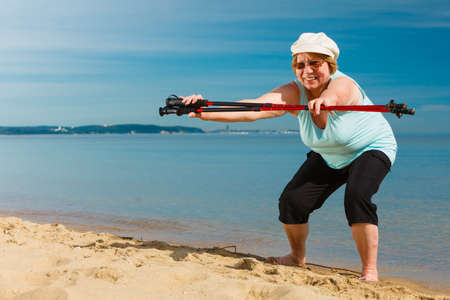 Senior woman enjoying nordic walking, doing warmup exercises with poles on sea shore, sunny summer day. Health, activity in old age. Stock Photo