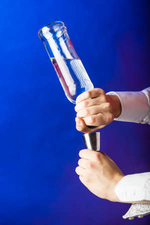 Party liquor flair bartending beverage concept. Filling shot glass from bottle. Person pouring alcohol.