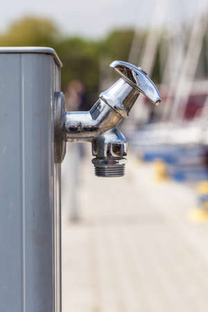 Hydration during walking concept. Small metal tap water outside for use by pedestrians. Stock Photo