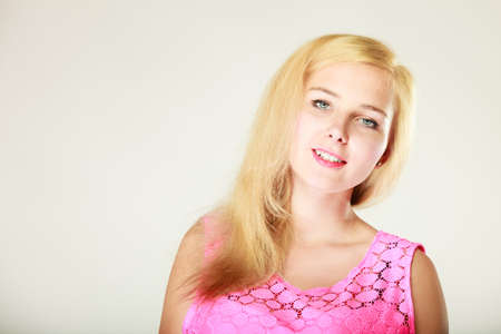 Dyeing, hairstyling, feminity, female beauty concept. Happy blonde woman in pink top. Studio shot on white background.