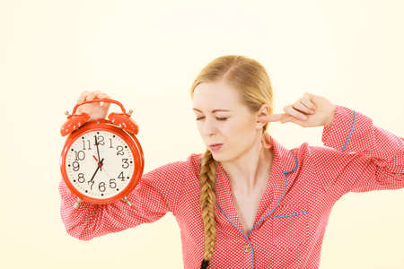Sleepy young woman wearing cute pink pajamas holding big red old fashioned clock showing sleep time pretending not hear alarm