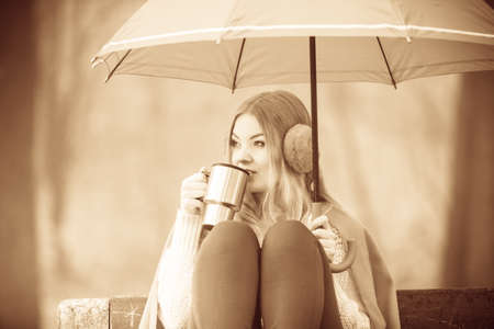 Happiness carefree and fall concept. Young woman relaxing in autumn park on bench under umbrella enjoying hot drink holding mug with warm beverage. Toned image