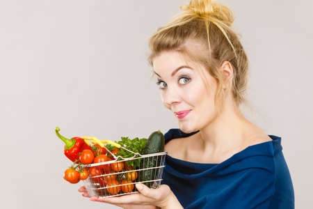 Buying good food, vegetarian products. Positive funny woman holding shopping basket with green red vegetables inside, recommending healthy high fibre diet, lifestyle modification, on grey Stock Photo