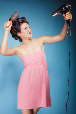 Young woman preparing to party having fun, funny girl styling hair with curlers hairbrush and hairdreyer retro style blue background Stock Photo