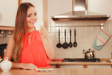 gingerbread: Pretty woman with heart shape gingerbread cookies drinking tea or coffee at home. Gorgeous young girl with hot beverage relaxing in kitchen. Stock Photo