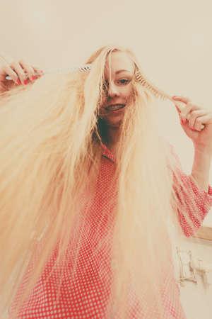 comb: Woman wearing pajamas in bathroom having fun while brushing her long blonde hair, windblown hairdo, shot from bottom.