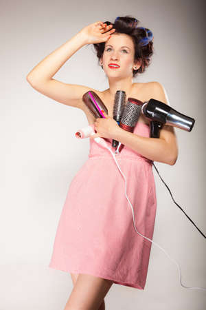 Young woman preparing for date having fun, cute girl with curlers styling hair with many accessories comb brush hairdreyer on  gray