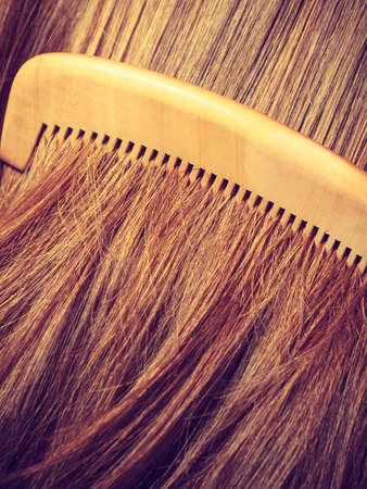 comb: Haircare concept. Straight brown hair with wooden comb closeup