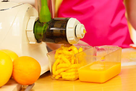 Woman young housewife in kitchen making fresh orange juice in juicer machine, preparing nutritious vitamin packed drink. Healthy eating, vegetarian food, dieting and people concept Stock Photo