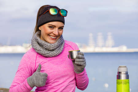 Woman athlete fit girl wearing warm sporty clothes outdoor in cold weather drinking hot tea from vacuum flask thermos, warming up. Sports, activities, hiking in winter or autumn time Stock Photo