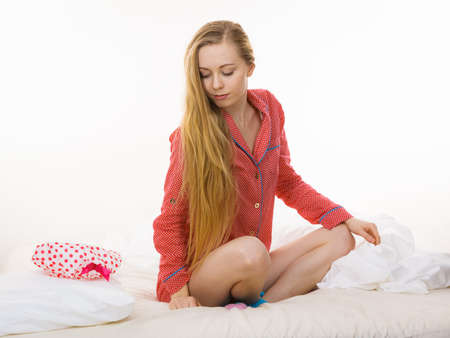 chillout: Teenage sleepwear fashion concept. Young woman lying on bed wearing cute pink pajamas combing hair with her fingers.