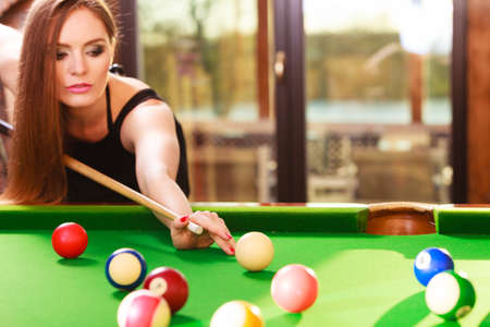 Competition concept. Young focused girl having fun with billiard. Pretty fashionable woman spending time on playing rivalry. Stock Photo