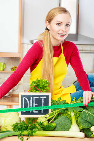 finocchio: Young woman in kitchen having many green vegetables presenting board with diet sign.
