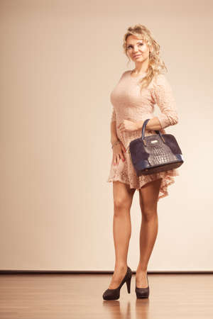 seduce: Fashion, people concept. Pretty, pensively lady with black handbag. Woman with high heels and beautiful beige dress. Stock Photo