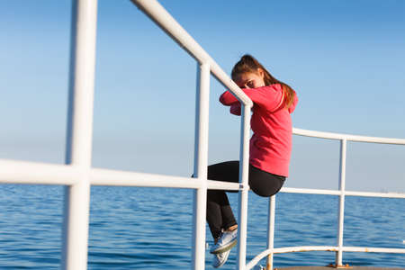 Outdoor, dangerous play, freedom and sport concept. Woman in sports suit sitting on handrail next to sea.