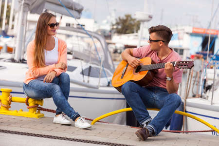 Love romance affection sound music talent concept. Girl charmed by musican. Young guitarist playing on the instrument in port. Stock Photo