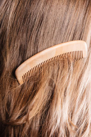 Haircare concept. Straight brown hair with wooden comb closeup