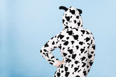 lady cow: Teenage girl in funny nightclothes, pajamas cartoon style, back view studio shot on blue.
