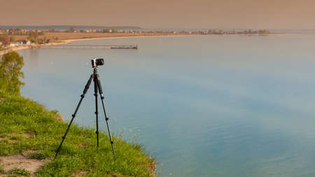 Photography in severe natural and weather conditions ideas concept. Camera with tripod on coastal cliff near water.